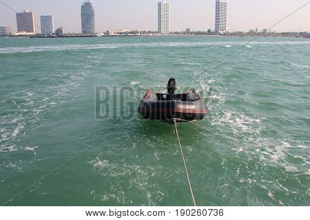 Black Motor Boat In The Ocean Tied To A Boat Against The Backdrop Of A Beautiful City