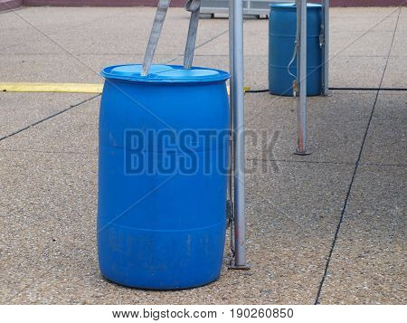 A plastic barrel filled with water is used to anchor down a pop-up tent for an event. There is one on each corner of the tent.