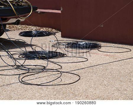 A master coil of electrical wire is slowly worked down to a few as contractors string new wiring for event tents.