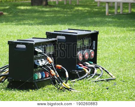 A large portable fuse box for electrical connections sits on the lawn of an event venue.
