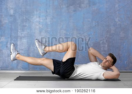 Handsome man doing bicycle crunch on color wall background