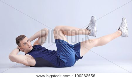 Handsome man doing bicycle crunch on light background