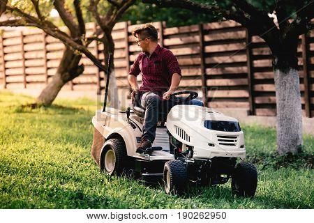 Gardner Mowing Backyard Grass With Motorised Vehicle. Landscaping Details
