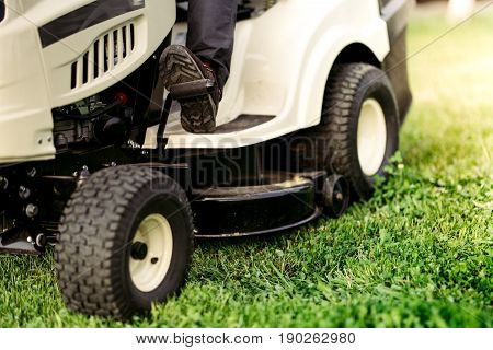 Ride-on Lawnmower Close Up Details Of Cutting Grass. Landscaping Industrial Details