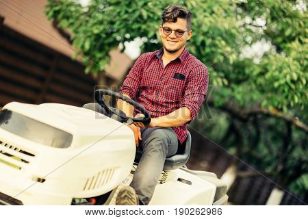 Lawn Mower Cutting Grass, Worker Portrait On Ride-on Tractor