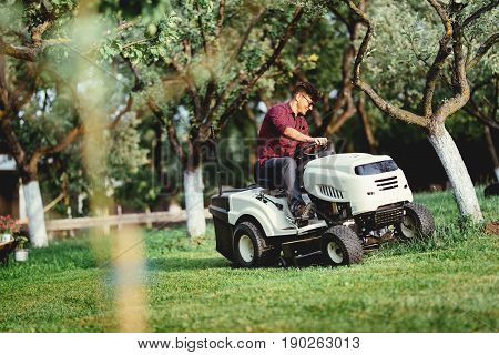 Gardening Details With Worker Using A Ride On Tractor, Mower For Cutting Grass