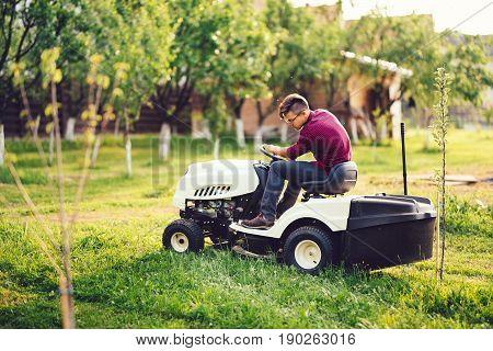 Gardening Details, Industrial Gardner Working With Ride-on Lawnmower And Cutting Grass In Garden