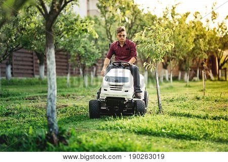 Fancy Gardner Cutting Grass, Using Professional Rideon Lawnmower And Doing Landscaping Works