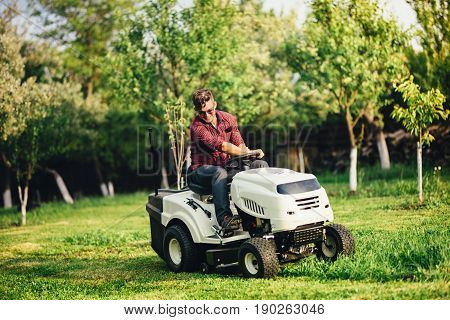 Portrait Of Industrial Worker Using Lawn Mower For Cutting Grass