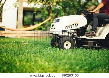 Landscaping Details - Worker Using Professional Tractor For Cutting And Trimming Grass
