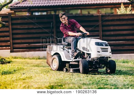 Gardening Works With Handsome Man Using Lawn Mower, Tractor And Industrial Tools