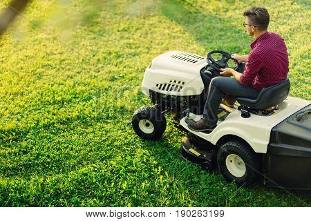 Gardening Works With Young Male Cutting Grass. Industrial Lawn Mower In Action