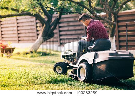 Male Worker Using Ride-on Lawnmower And Cutting Grass Through Garden