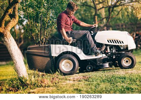 Professional Male Landscaper Using Lawn Mower For Cutting Grass In Home Garden