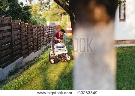 Male Worker Riding Lawn Mower And Trimming Grass In Garden
