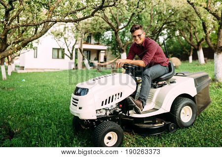 Gardening Details, Grass Trimming In Progress. Male Worker Using Lawnmower And Smiling