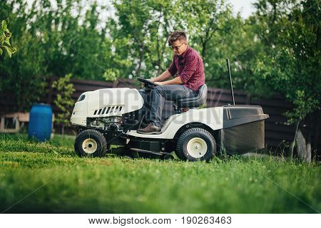 Worker Using Lawn Mower For Cutting Grass In Garden