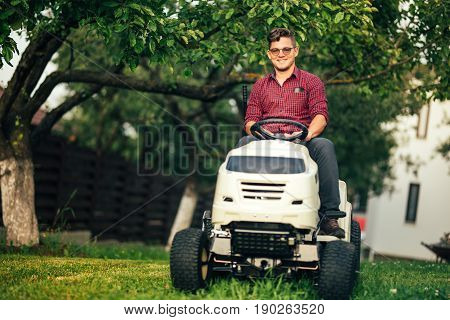 Lawncare Concept - Smiling Worker Using Ride On Grass Mower