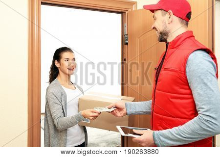 Young woman paying for parcel received from courier