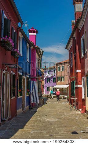BURANO, ITALY - MAY 23, 2017: Walking in the colorful street of Burano island, Veneto