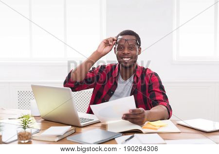 African-american businessman in office, work with laptop and documents with pleasure, looking at camera