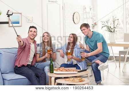 Friends taking selfie while eating pizza at home