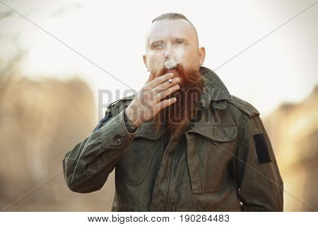 Bearded man smoking weed outdoors