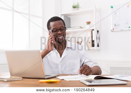 Satisfying call. Young black businessman talking on mobile and making notes in modern white office interior.
