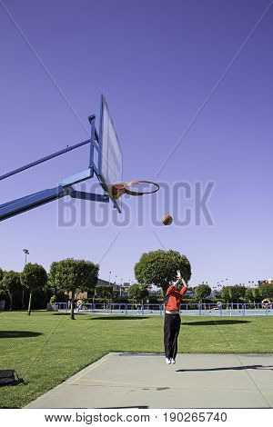 Young playing basketball sports center  in city