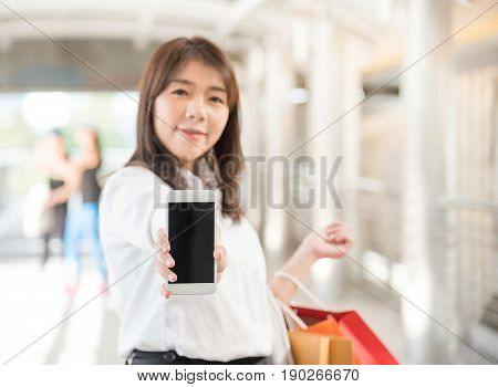 Front view of a shopper holding shopping bags showing to the camera a blank smart phone screen with an urban background. Focus on hand holding mobile phone with clipping path and copy space.