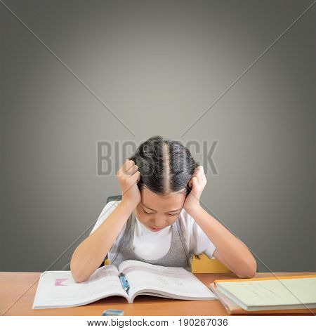Stressed schoolgirl doing homework and preparing for exams. Young Asian student girl hard at work reading book isolated on grey background and copy space. Education concept.