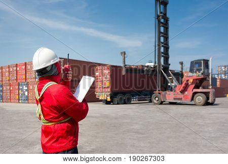 Foreman control loading Containers box from Cargo freight ship for import and export