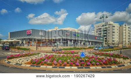 Nes Ziona, Israel-March 20, 2016:  Beautiful view of big flowerbed placed on traffic circle in front of supermarket Mega In The City and other commercial stores. Nice blue sky is over it. The complex is located at 1 Avner Ben Ner Street. Two white multi-s
