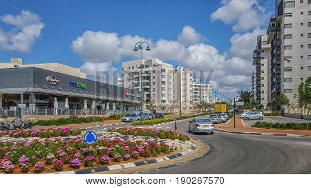Nes Ziona, Israel-March 20, 2016: Front view of beginning of Avner Ben Ner street. New modern multi-story residential buildings are located on both sides of it. There are supermarket and other commercial stores in left side and beautiful traffic circle in