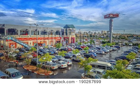 Rishon LeZion Israel-April 12 2016: Side view of large DIY store Home Center and big parking lot full of cars in front of it. It was raining recently. Wet asphalt and beautiful clouds in the sky. Horizontal shot. It is located at 4 Lehi Street.