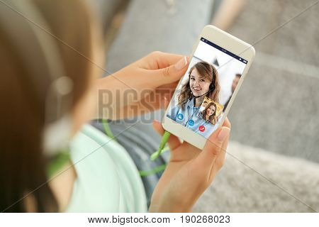 Concept of online taxi service. Woman video conferencing with dispatcher on smartphone, outdoor