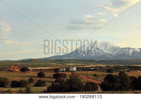 Scenic summer Colorado landscape in Rocky Mountains with farmhouse on sunset.