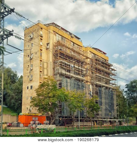 Rishon LeZion, Israel-February 18, 2016: Shabby 8 story residential building is being covered by steel and wooden scaffolding and mesh. Exterior balconies are being built to this condominium. At the end it will be painted. It  is located at 33 Ben Gurion