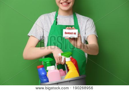 Chambermaid holding business card with text CONTACT US and cleaning supplies on color background. Recruitment concept