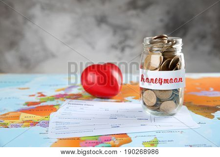 Money savings for honeymoon in glass jar and tickets on world map