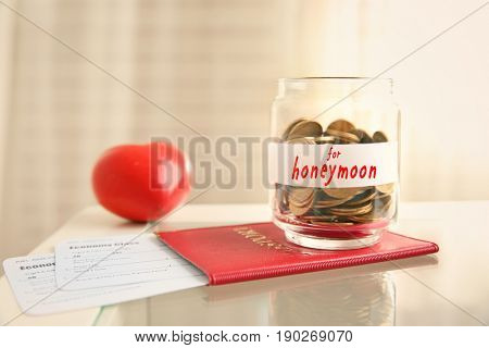 Passport with tickets and money savings for honeymoon in glass jar on table