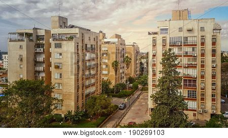 Nes Ziona Israel-March 20 2016: View of old four residential 8 story buildings are located at Anielewicz Street. Two big green trees grow in front of facades in the foreground. Cloudy sky. Horizontal shot