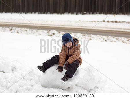 warmly dressed boy walking on a winter street