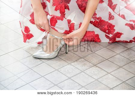 Close up hand of woman or bride in beautiful dress tied a shoelace on her silver high heel shoes. Copy space.