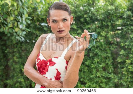 Portrait of Asian trans woman or trans gender smoking cigarette in garden. People smoking and bad habits concept. Picture for World No Tobacco Day.