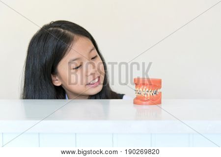 Artificial model of human jaw with dental braces in front of Asian pre teen girl with clean overbite tooth smiling in orthodontic office or clinic. Pediatric dentistryeducation and prevention concept