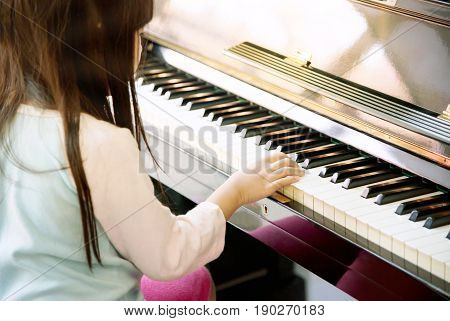 Back of adorable female kid playing piano at home. Close up of Asian cute girl practicing piano in music class.