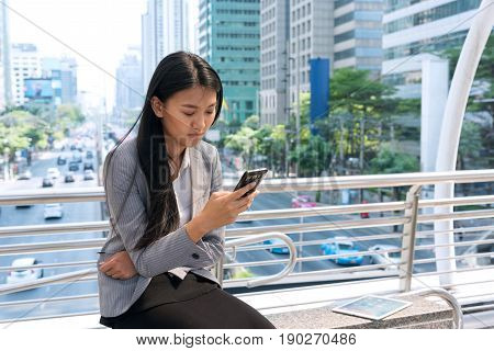 Young businesswoman sitting outdoor with mobile phone reading text messages on cell phone. Asian girl holding and typing message in smart phone in city with background of urban landscape. Copy space.