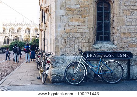 OXFORD, UK - MAY 22, 2017: Bicycles parked against the building in Oxford, tourists taking photos on the background. Cycling is a popular way of getting around the city.