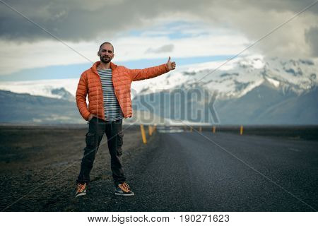Travel hitchhiker man on a road